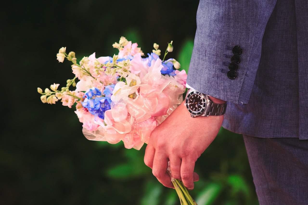 Fotografia ślubna Grupa 5D z Bydgoszcz - zbliżenie na rękę Pana Młodego trzymającego bukiet dla przyszłej żony.