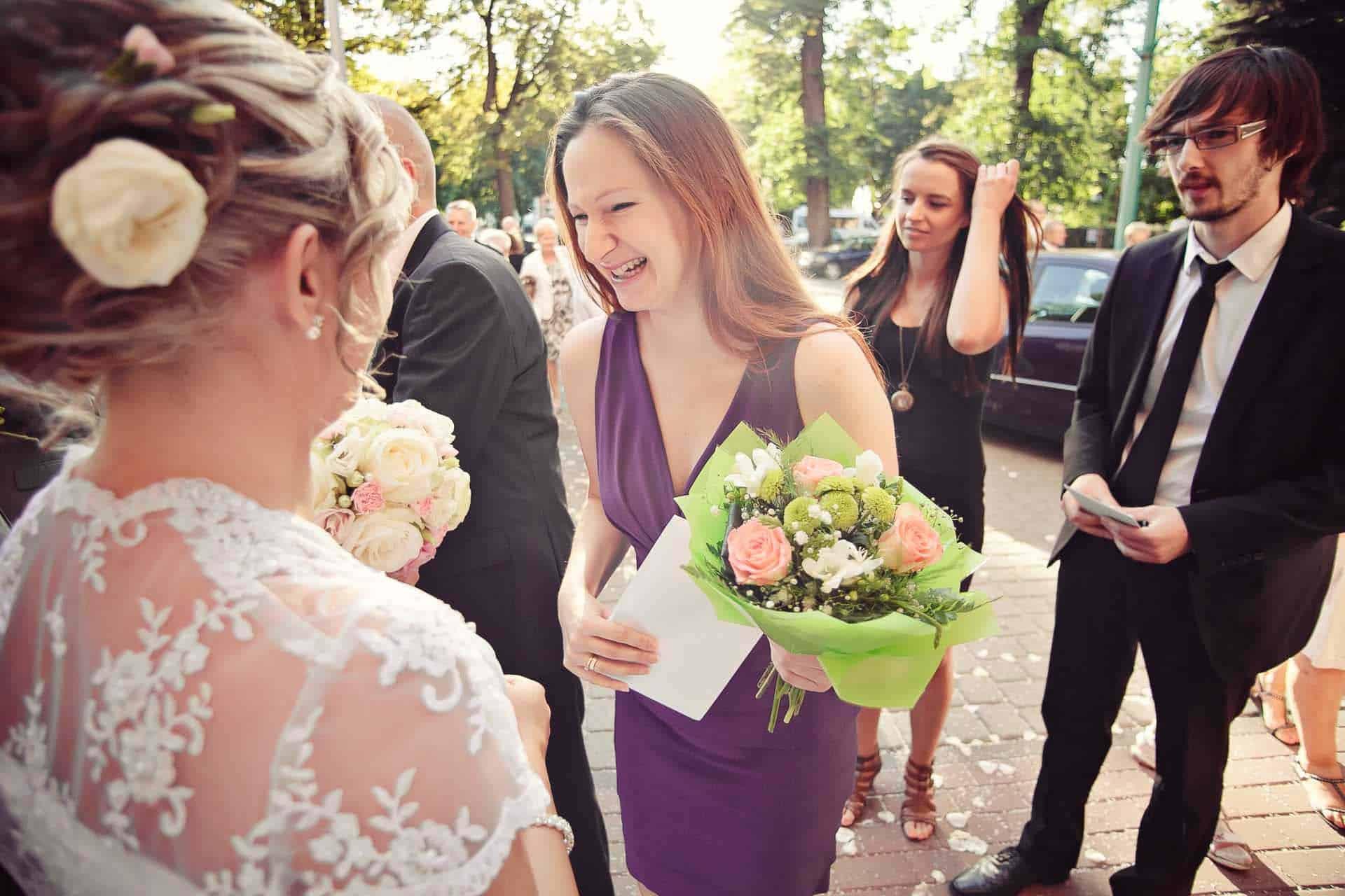Fotografia ślubna po ceremonii w kościele - życzenia od najbliższych.