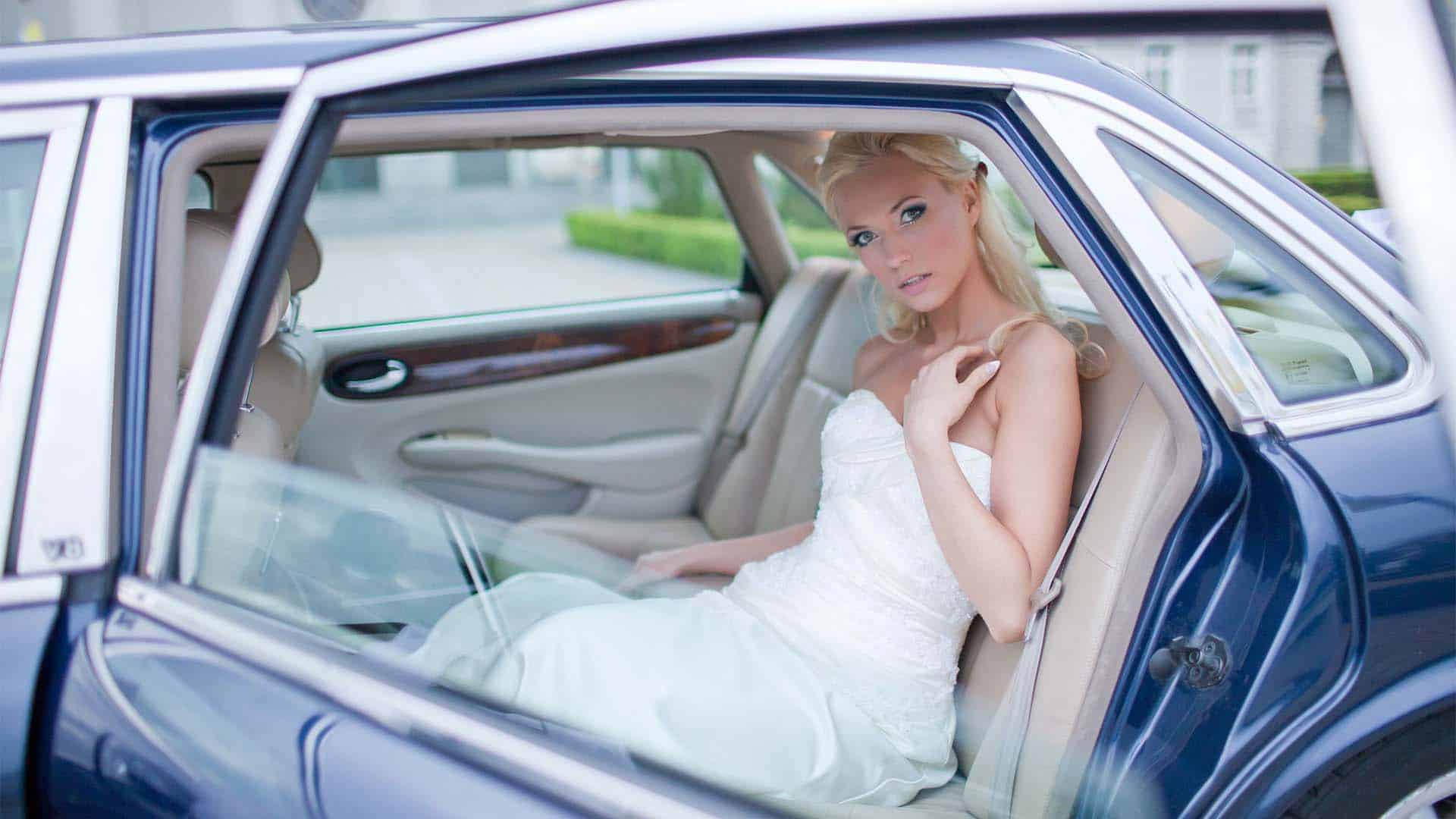 Panna Młoda wysiada w limuzynie ślubnej - fotografia z ceremonii ślubu.