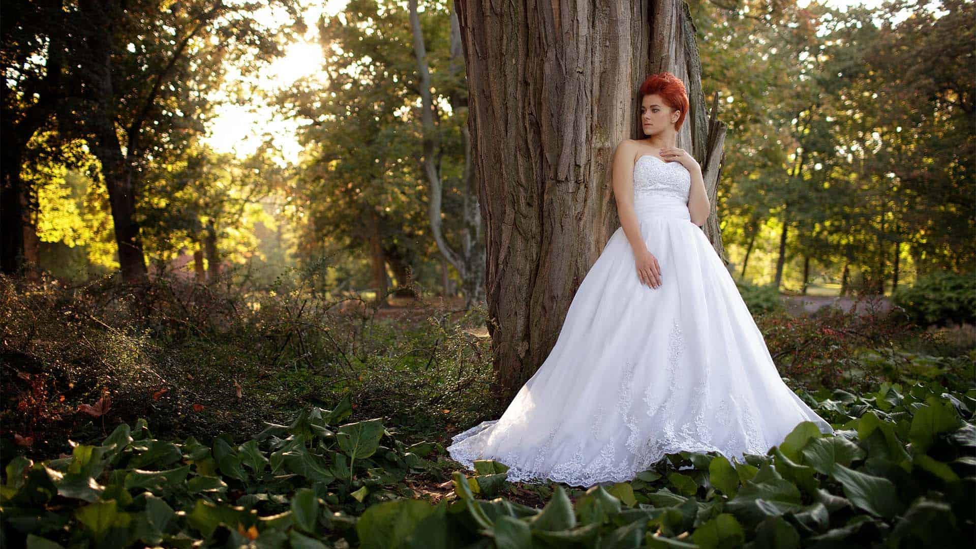 Panna Młoda - Karolina - kryje się w cieniu drzew - zdjęcie ślubne w plenerze