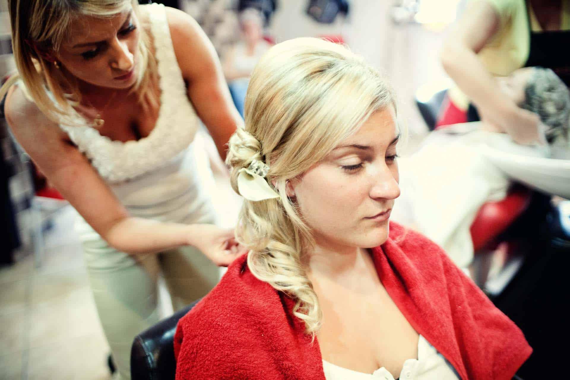 Fotografia z przygotowań - Panna Młoda u fryzjera przygotowuje fryzurę ślubną.