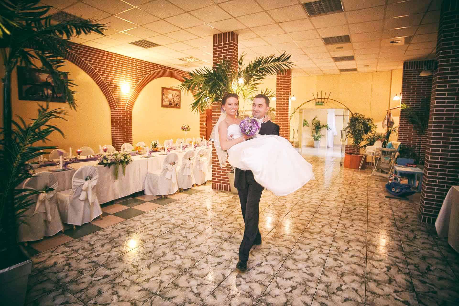 Pan Młody przenoszący Pannę Młodą przez próg na zdjęciu z wesela - Grupa 5D.