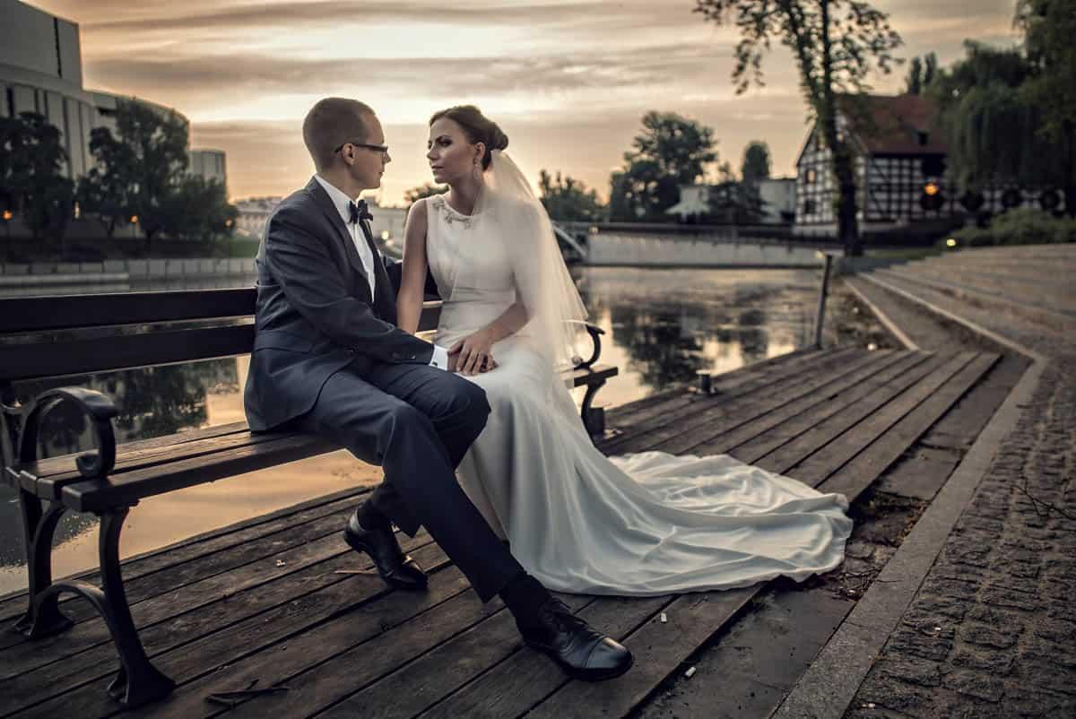 Szymona i Eliza podczas pozowania do zdjęcie ślubnego na ławce.
