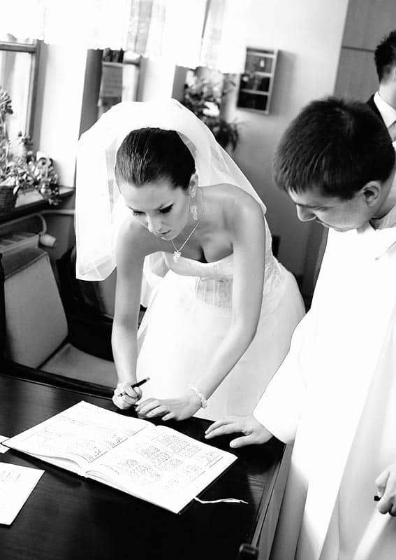 Panna Młoda przy podpisywaniu aktu ślubu - fotografia ślubna z kościoła w Bydgoszczy
