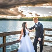 Państwo Młodzi po ślubie na pomoście przy jeziorze.