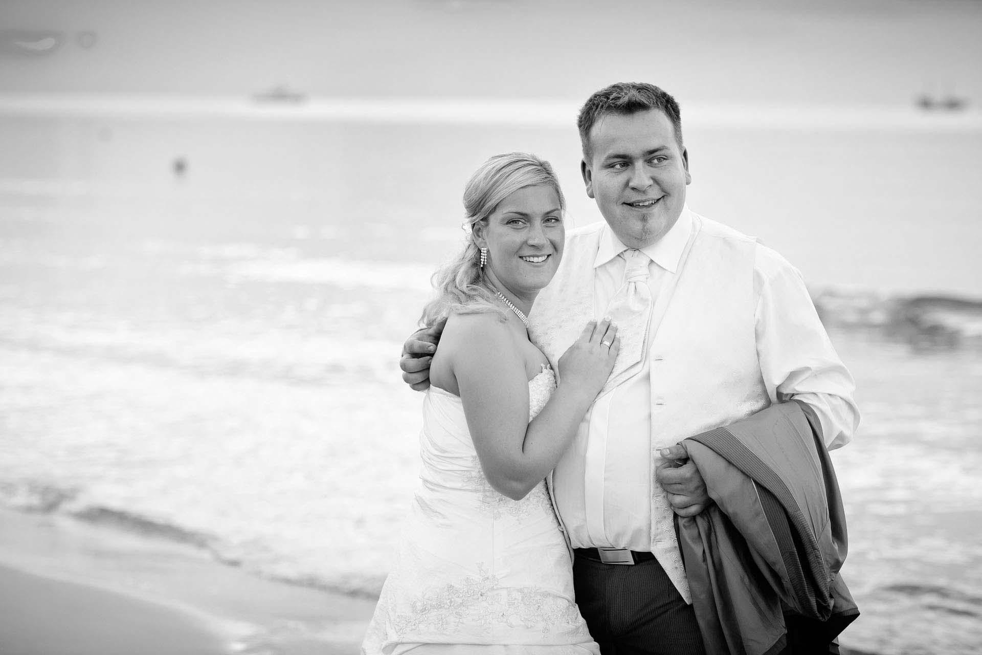Czarno-białe foto Pany Młodej na piaszczystej plaży z fotograficznej sesji ślubnej.