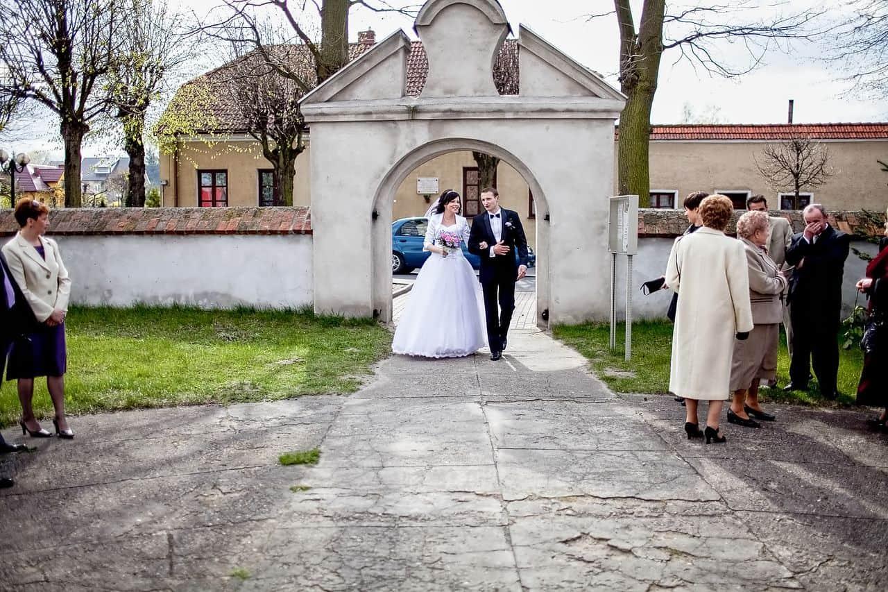 Państwo Młodzi przed wejściem do kościoła - fotografia ślubna.