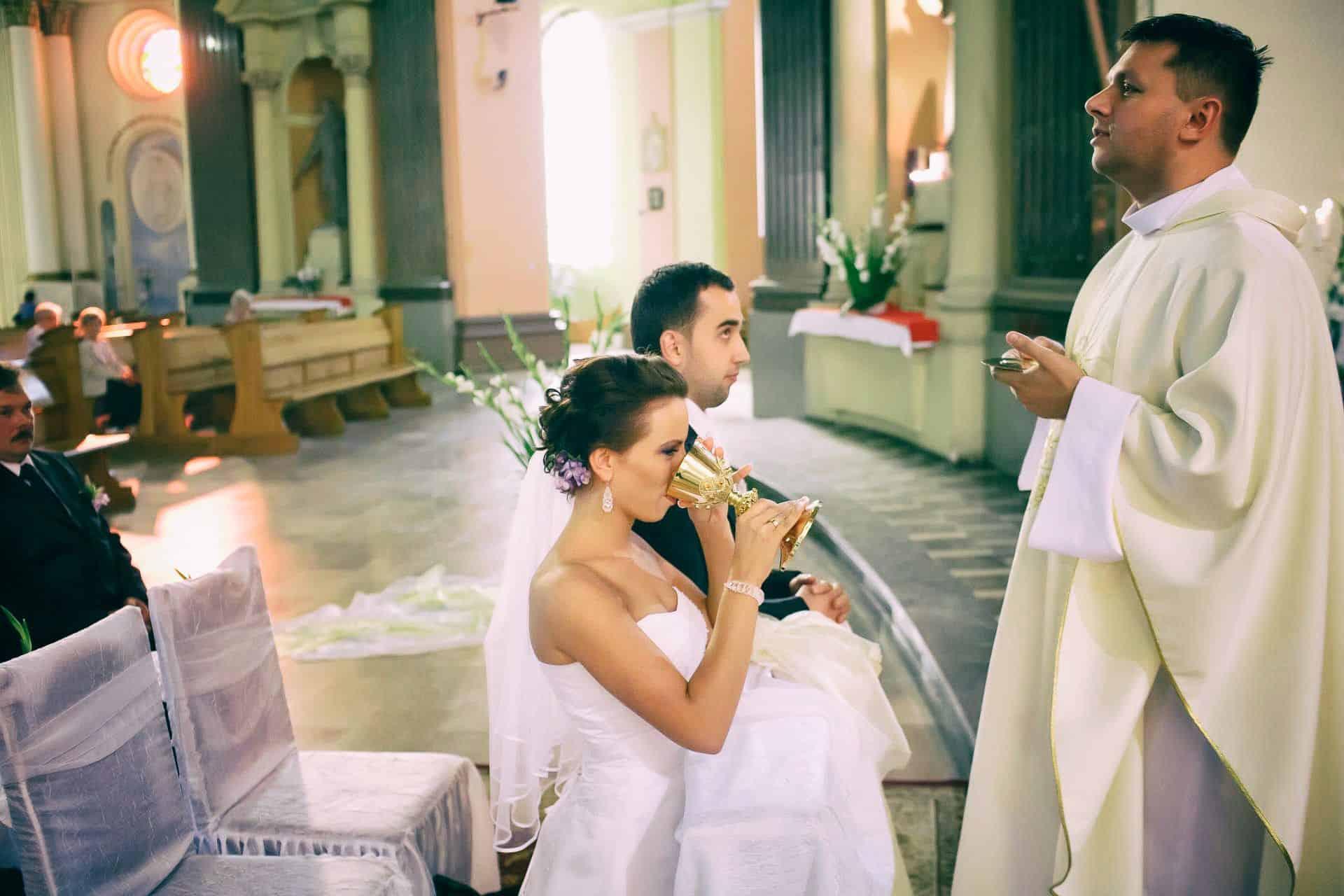 Państwo Młodzi podczas przyjmowania komunii świętej na fotografii z ceremonii zaślubin.